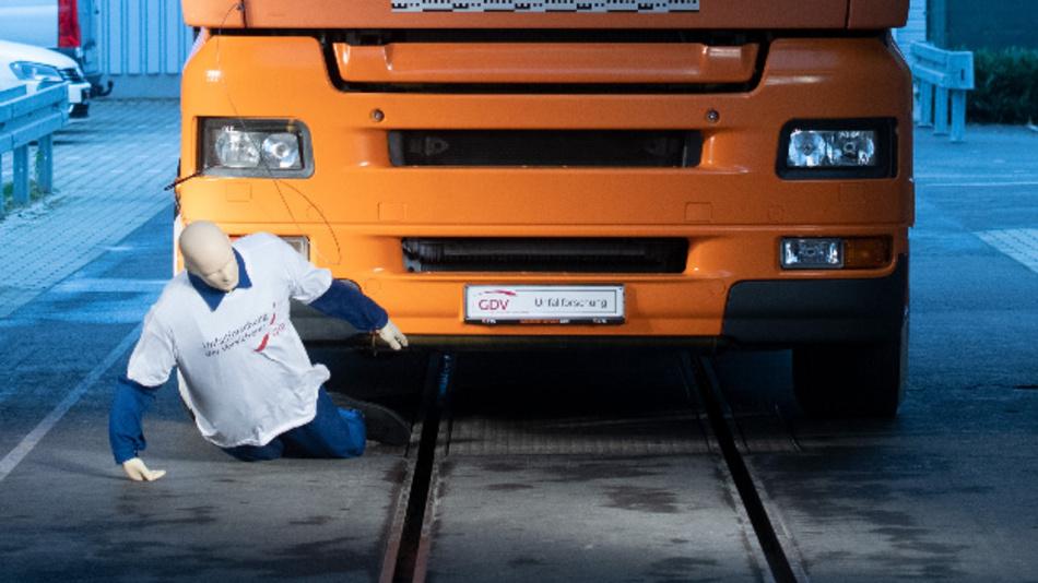 Ein Puppe wird bei einem Versuch der Unfallforschung der Versicherer von einem LKW angefahren.