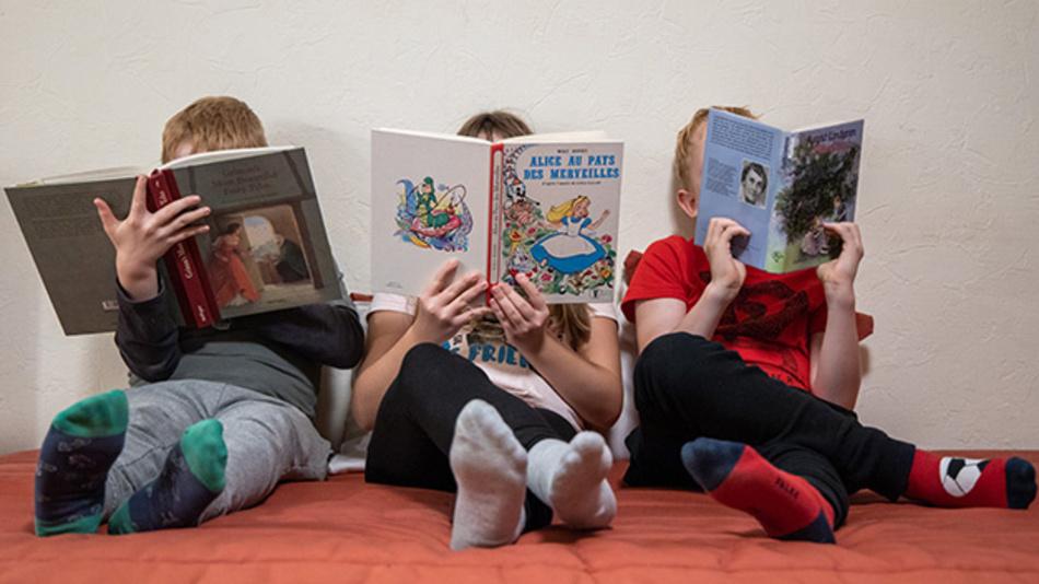 Drei Kinder lesen jeweils ein englisches (l), ein französisches (M) und ein deutsches Buch.