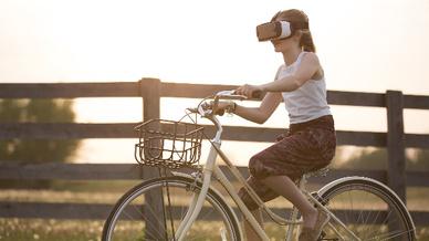 Mädchen auf Fahrrad trägt VR-Brille.