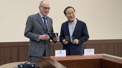 Dr. Andreas Wendt, Vorstandsmitglied für Einkauf und Lieferantennetzwerk von  BMW und Young-Hyun Jun, CEO von Samsung SDI unterzeichnen den Langzeit-Liefervertrag.