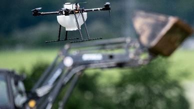 Eine Drohne fliegt vor einem Traktor über einem Getreidefeld. Mit digitaler Technik sollen gleich mehrere Fliegen mit einer Klappe geschlagen werden: den Landwirten die Arbeit erleichtern und den Umweltschutz verbessern.