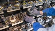 Ein Mitarbeiter eines Maschinenbauers nimmt Bohrer aus einem Regal.