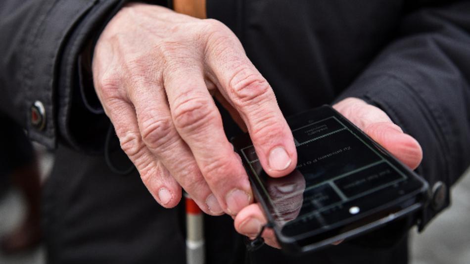 Ein blinder Mann hält ein Smartphone mit der Verkehrs-App InMoBS in der Hand.