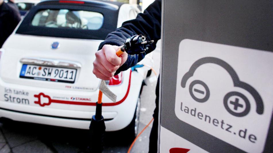 Ein Mitarbeiter der Stadtwerke Aachen schließt ein Elektroauto an eine Ladestation in der Kölner Innenstadt an.