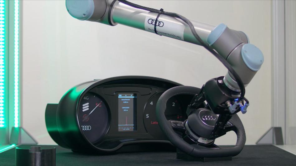 Ein industrieller Roboter baut ein Airbag-Modul in das Lenkrad eines Audi ein.