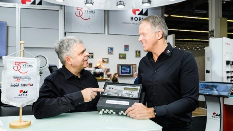 Udo Metzulat (links) und Thomas Lüke (rechts) von Bopla am Messestand mit einem Gehäuse für ein Kompressoren-Leitsystem aus dem Jahr 1993.