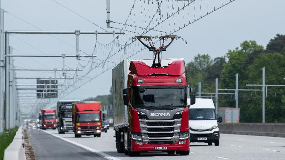 Eine Scania R450 Hybrid Zugmaschine (M) fährt mit ausgefahrenem Stromabnehmer während der Inbetriebnahme der ersten deutschen Teststrecke für E-Lastwagen mit Oberleitung auf der Autobahn 5 (A5).