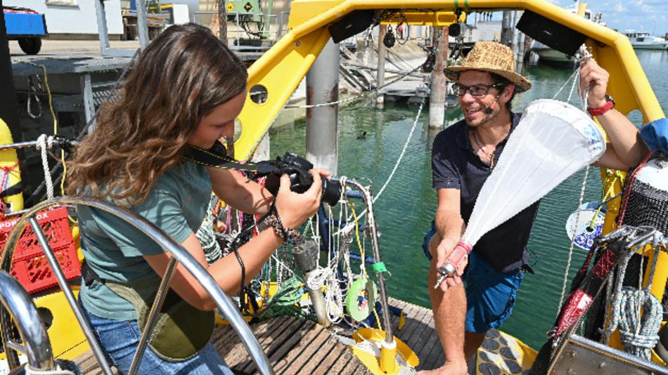 Gewässerökologe Hannes Imhof (r) erklärt Anne Hartig an der Kamera, wie ein Planktonnetz funktioniert. In Corona-Zeiten zeigen sie, wie sie Schüler aus Baden-Württemberg virtuell in Expeditionen und Untersuchungen mit einbeziehen können.