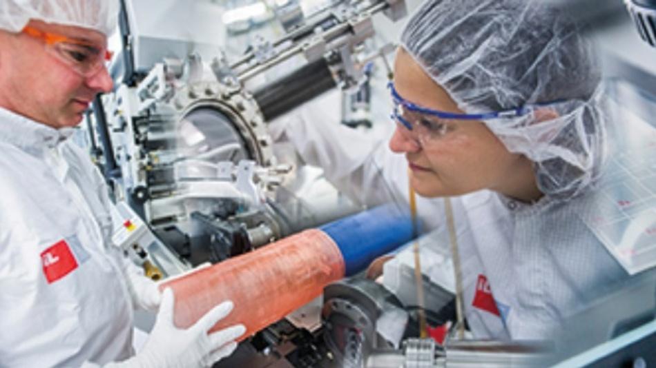 """Eine Rolle-zu-Rolle Druckanlage, bei der ein Mitarbeiter eine neue Druckform auf die Vorrichtung aufbringt. In der Mitte schaut eine Mitarbeiterin in das """"Clustertool"""", ein vernetztes Ultrahoch-Vakuumsystem zur Präparation und Analyse von Proben."""