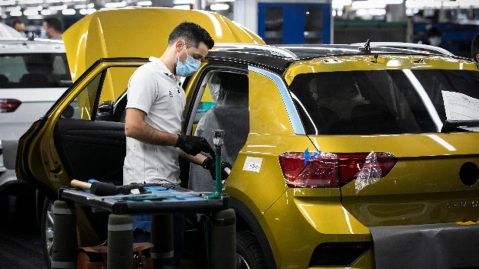 Portugal, Palmela: Ein Angestellter mit Mundschutz arbeitet an der Montagelinie an einem Volkswagen T-Roc im portugiesischen Autowerk von Volkswagen Autoeuropa. Das Werk nahm nach anderthalb Monaten, in denen durch die Corona-Pandemie nicht produziert wurde, die Produktion wieder auf.