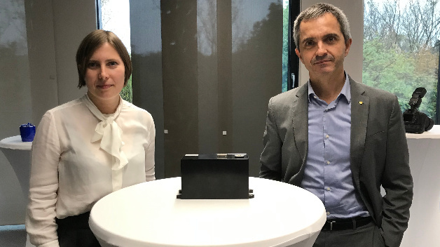 Dr. Lucía Cabo (left) is Manager Basic R&D Film Capacitors and Fernando Rodríguez (right) is working in the Application and Modelling Group, both at TDK. On the table there is a sample of the newly developed film capacitor for wide bandgap semiconductors.