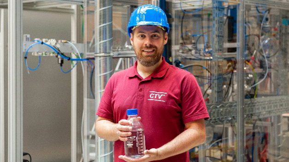 Prof. Dr.-Ing. Jakob Burger, Professor für Chemische und Thermische Verfahrenstechnik, vor seiner neu errichteten Demonstrationsanlage am TUM Campus Straubing für Biotechnologie und Nachhaltigkeit. Die Flasche enthält auf dieser Anlage hergestellten Oxymethylen-Ether (OME).