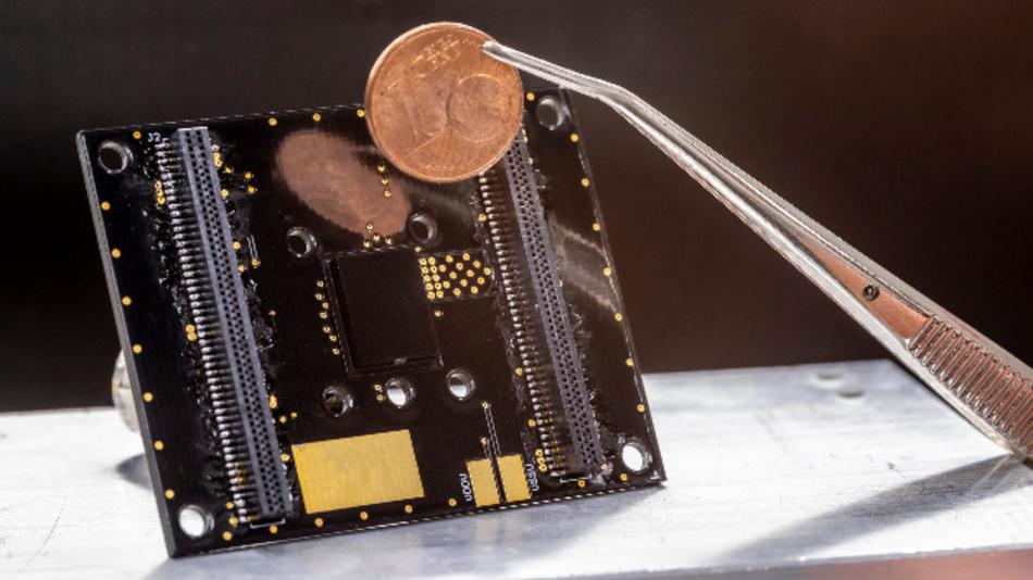 Der an der TU Graz entwickelte Prototyp des Partikelsensors (das schwarze Quadrat in der Mitte der Platine) im Größenvergleich mit einer Ein-Cent-Münze.