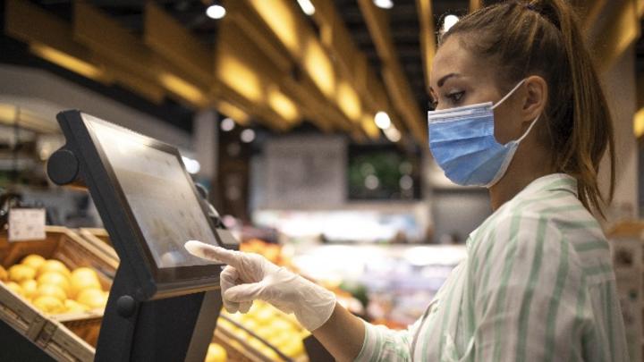 Frau mit Mundschutz und Handschuh berührt Display im Supermarkt.