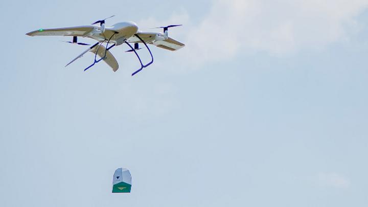Eine Drohne des Start-Ups Wingcopter trägt ein Paket. So könnten sie Corona-Impfstoffe in entlegene Gegenden der Welt auszuliefern.