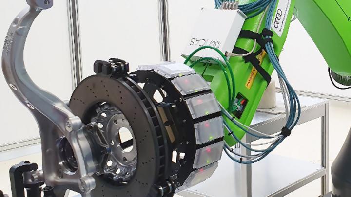 Demonstrator im Audi-Testlabor: Radarsensor-Ring am Fanuc-Fertigungsroboter, der eine Bremsscheibe in Position hält.