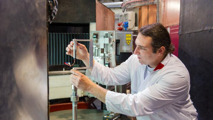 Martin Mühlbauer montiert eine Lithium-Ionen-Zelle im Objektträger des hochauflösenden Pulverdiffraktometers (SPODI) am FRM II.