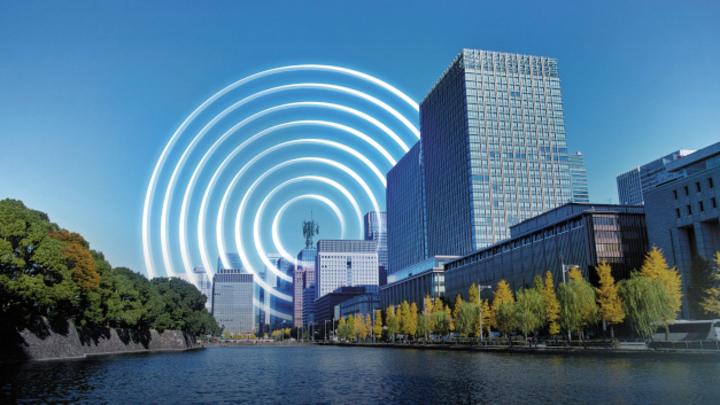 Foto einer Stadt am Fluss mit Mobilfunksendeanalge und Funkwellen.