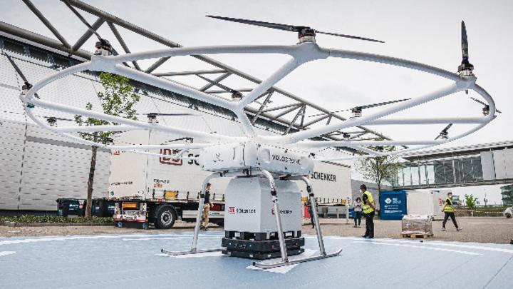 Der erste Testlauf auf der Messe Stuttgart: Eine Volodrone  nimmt die Nutzlast auf, die ein autonomer mobiler Roboter von Gedeon Brothers bereit gestellt hat.
