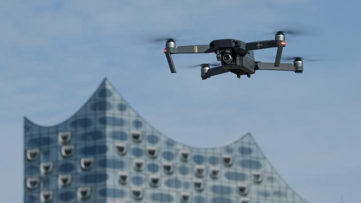 Eine Drohne, die mit einer Foto/Videokamera ausgestattet ist, schwebt in Hamburg in der Nähe der Elbphilharmonie am Himmel. Der Hamburger Hafen ist das bundesweit erste Testfeld für ein Drohnen-Verkehrssystem in Deutschland.