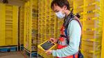 Philipp Weiß kontrolliert bei der Firma Amazon mit einem Tablet Logistikroboter.