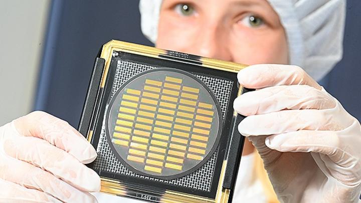 Ingenieurin Hannah Wagenknecht hält einen Wafer mit neuentwickelten Chips zum Einsatz in Quantencomputern.