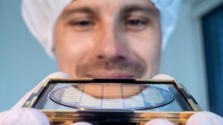 Ein Mitarbeiter von Q.ANT zeigt einen Wafer, auf dem die optischen Quantencomputer-Chips entstehen, die Trumpf-Tochter Q.ANT entwickelt und Trumpf Photonic Components fertigen wird.