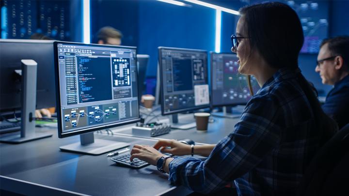 Smart Female IT-Programer, der am Desktop-Computer im Rechenzentrum arbeitet. Team von jungen Profis, die Programmierung von Code durchführen.